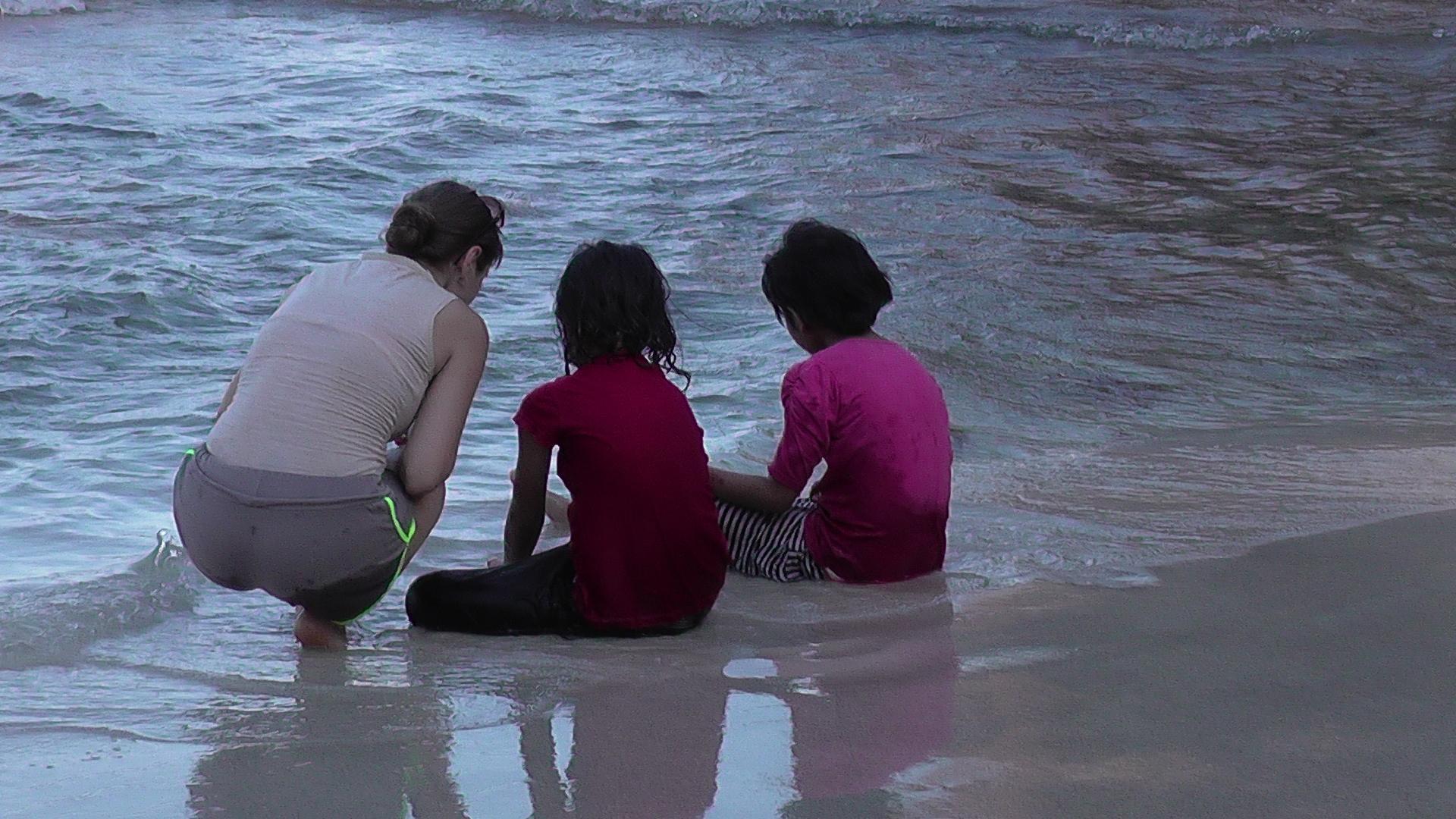Voluntärin mit Kindern am Strand