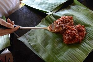 Man wickelt man den mit Sauce bedeckten Fisch in Bananenblätter