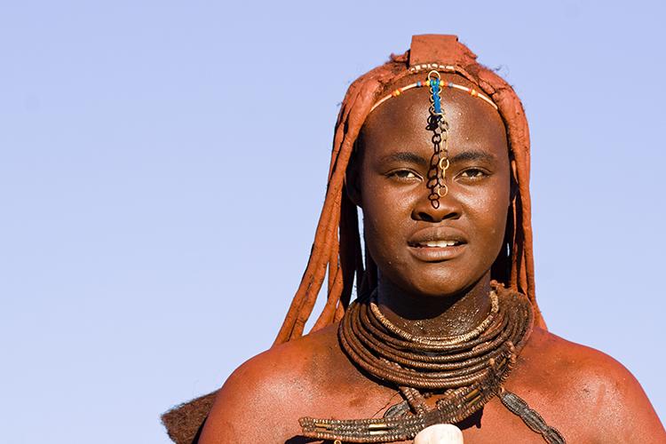 Eine stolze Frau des Himba-Volkes. Um sich vor der Sonne zu schützen, reiben sich die Himba täglich mit Ockerpaste ein, eine Mixtur aus zerstoßene roten Steinbrocken und Kuhfett.
